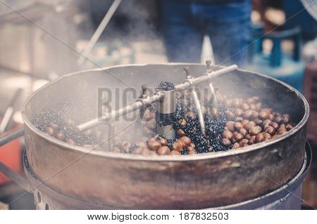 Roasting chestnuts with traditional machinery in a vendor in Kuala Lumpur Chinatown, Malaysia