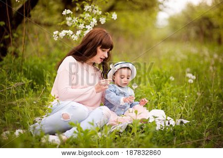 Mom for a walk in the garden with a little daughter holding a dandelion