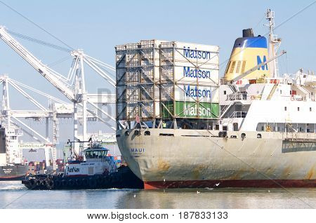 Oakland CA - May 22 2017: Tugboat SANDRA HUGH pushing on the stern of Matson cargo ship MAUI turning the vessel 180 degrees prior to docking at the Port of Oakland.