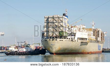 Oakland CA - May 22 2017: Tugboats are small but powerful for their size. Tugboat SANDRA HUGH pushing on the stern of cargo ship MAUI turning the vessel 180 degrees prior to docking at the Port of Oakland.