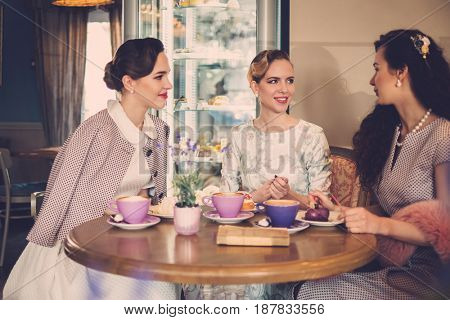 Three elegant young ladies in a cafe