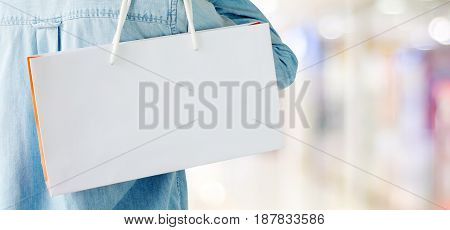Hand holding white shopping bag on blur store background banner with copy space for text template business concept