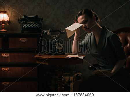 Upset woman with letter in retro interior