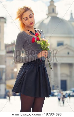 Young girl in love. Blonde teenager with roses in hand. Standing in the city center holding roses in hand. Looking down and lost love. The historic center of Rome, Italy as background.