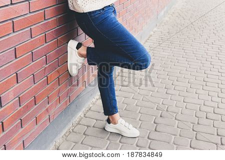 Girl is standing near the wall in blue jeans and white sneakers. Copy space