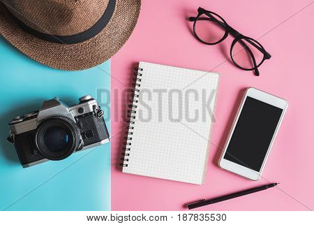 Flat lay fashion style with camera smart phone notebook and hat on pastel color background with copy space Top view