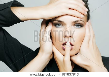 woman with hands touching pretty face with freckles of adorable girl fashion model with young healthy skin sexy lips stylish fashionable makeup on grey background. Beauty and skincare