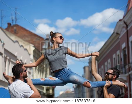 girl or pretty woman fit model in stylish sunglasses and blue jeans sitting leg split on shoulders of two bearded handsome men on sunny summer day on city street. Active lifestyle friends