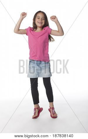 Girl jumping with arms raised