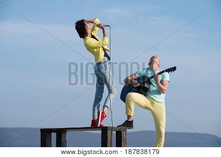 woman singer or girl singing on table and handsome man guitarist playing acoustic guitar on sunny summer day on blue sky. Young musicians performing on nature. Music concert and performance