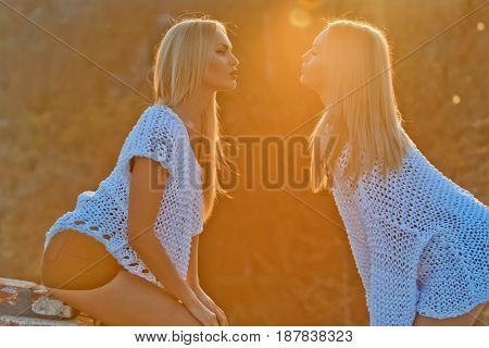 girls or twin women lesbian girlfriends with long blond hair in fashionable white sweaters air kissing on sunny day on natural background. Homosexual couple in love