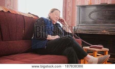 ortrait of elderly woman in home clothes, sitting on a brown sofa and talking on the house phone