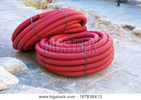 Stack new red PVC pipe lay on a construction site for laying electric cable.