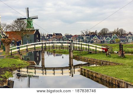 ZAANS SCHANS, NETHERLANDS - APRIL 1, 2017 Wooden Windmill White Bridge Reflection Zaanse Schans Old Windmill Village Countryside Holland Netherlands. Working windmills from the 16th to 18th century on the River Zaan.