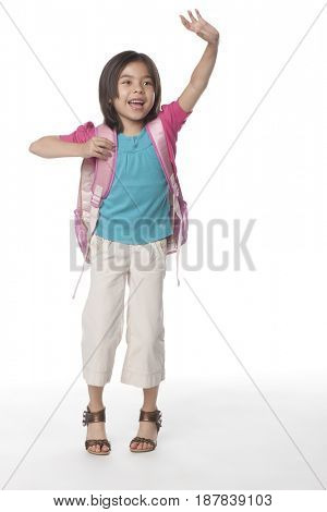 Mixed race girl with arms raised carrying backpack