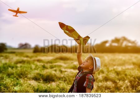 a boy plays with a model airplane during sunset. Dream to be a pilot