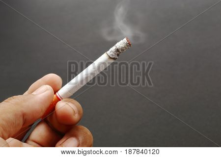 Smokers hand with cigarette burning on dark background.
