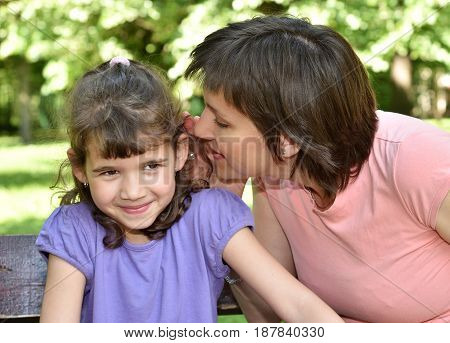 Mother whispering secret into ears of smiling daughter
