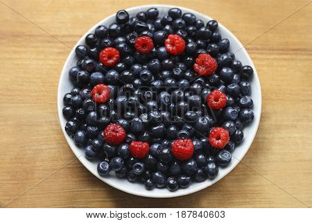 Plate with berries on a wooden surface. Raspberries and blueberries sprinkled on a white plate