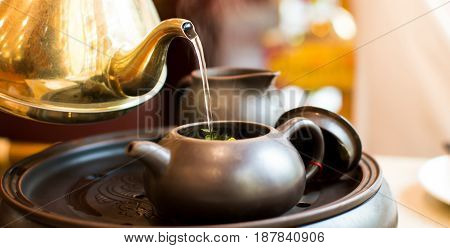Hot Water Pouring Into Ceramic Teapot