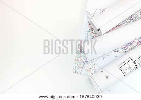 Rolls Of Construction Plans And Draft Land-use Project On White Desk