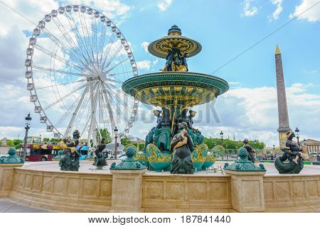 Paris France - May 3 2017: Fountain of the Rivers at the center of the Place de la Concorde with The Obelisk of Luxor and The Big Wheel in a background cloudy on May 3 2017 in Paris France.