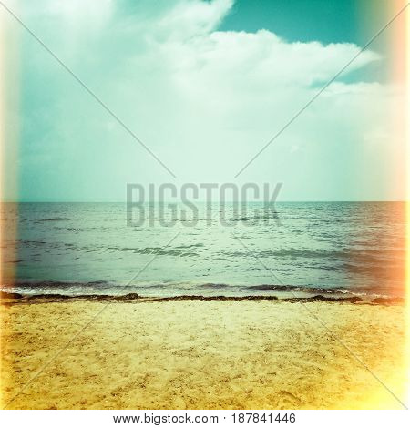 Sea and summer beach. Retro style photo with light leaks.