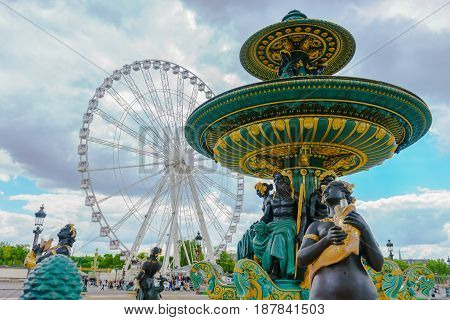 Paris France - May 3 2017: Fountain of the Rivers at the center of the Place de la Concorde with The Big Wheel in a background cloudy on May 3 2017 in Paris France.