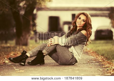 Young fashion woman with long curly hairs sitting on city street. Stylish female model in a sweater and blue jeans