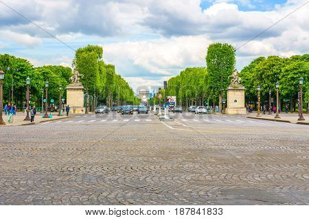 Paris France - May 3 2017: Road traffic conditions of Champs-Elysees Avenue views from Place de la Concord with blue cloudy day background on May 3 2017 in Paris France.