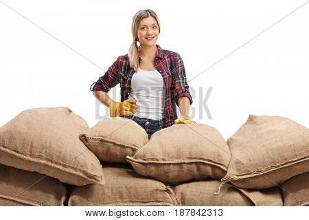 Female farmer behind a pile of burlap sacks looking at the camera isolated on white background