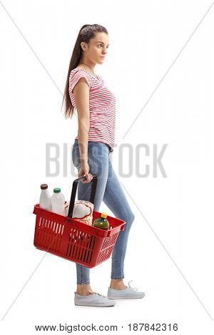 Full length profile shot of a teenage girl with a shopping basket waiting in line isolated on white background