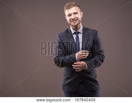 Young Man In Suit Adjusts His Cuffs