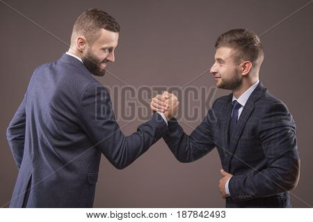 Two men in suits struggling in his arms looking into each other's eyes