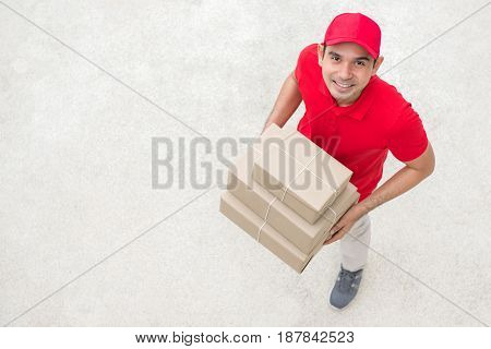 Delivery man in red uniform holding parcel box - topview