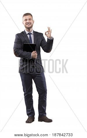 Businessman standing in suit with laptop in his hands and showing sign of ok