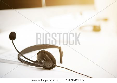 Microphone headsets on the table with computer keywords - call center concept