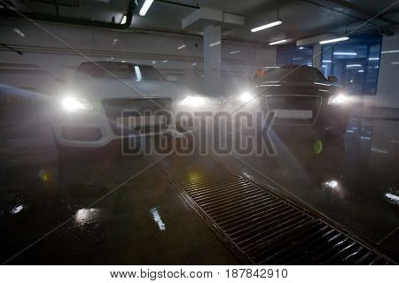 Black and white same vehicles illuminating sprayed water with headlights in car wash station.