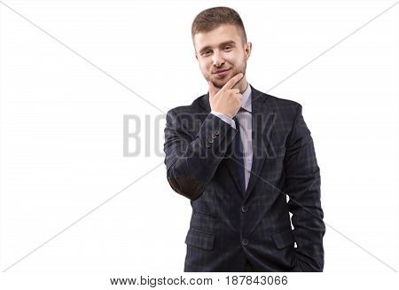 Young man in a suit stroking his beard with a smile