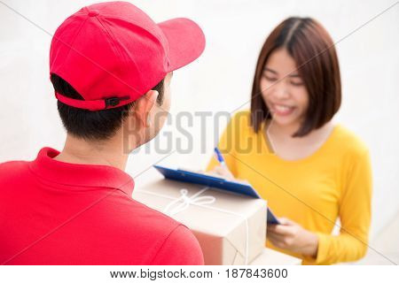 Postal delivery man delivering parcel boxes to a woman