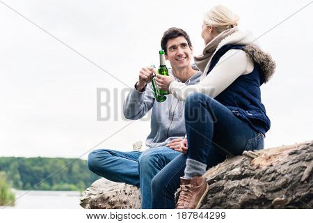 Young couple, woman and man, sitting on tree stump at the riverside drinking beer and saying cheers
