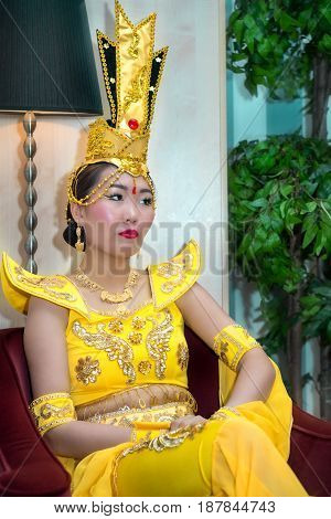 Young asian woman in yellow traditional chinese stage costume sitting on the armchair