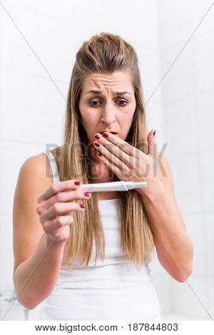 Young woman in desperation about the result of her pregnancy test looking at the strip