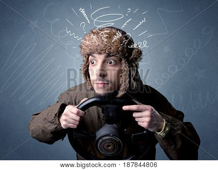 Young man holding black steering wheel with white scribbles around him