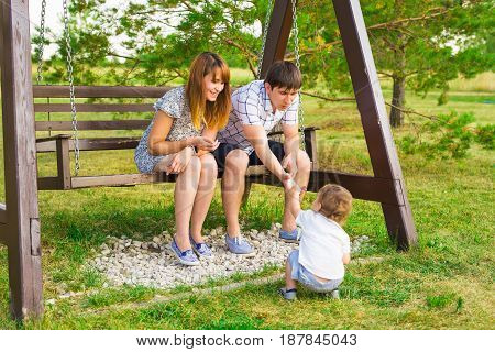 Mother, father and child son playing together outdoors.