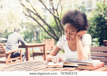 Afro female college student reading book in the garden
