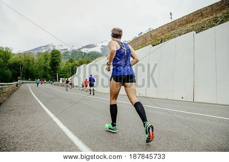 Rosa Khutor, Russia -  May 7, 2017: back group of runners athletes running road in race Spring mountain marathon