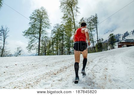 Rosa Khutor, Russia -  May 4, 2017: back male runner running on snow mountain trail  in race Vertical kilometer