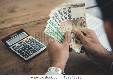 Hands of businessman holding money South Koren won banknotes at working desk