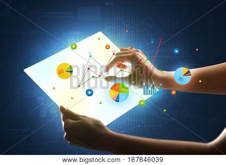 Young female hand holding a tablet with colorful charts